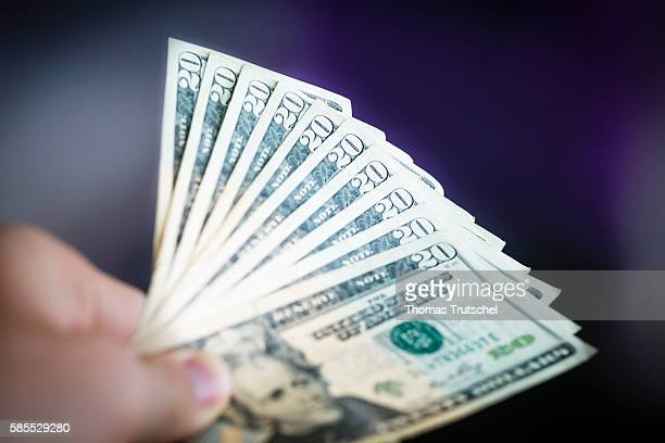In this Photo Illustration a person holds Dollar banknotes on August 03 2016 in Berlin Germany