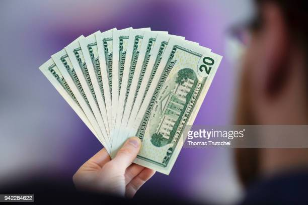 In this photo illustration a person is holding dollar bills in hand on April 05 2018 in Berlin Germany