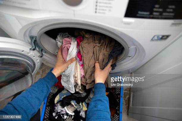 In this photo illustration a person is putting clean laundry in a basket on April 13, 2021 in Bonn, Germany.