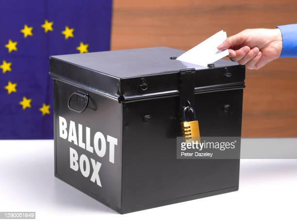 In this photo illustration, a person puts a voting slip into a ballot box with the EU flag behind it on December 8,2020 in London, England.