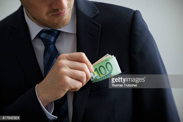 In this Photo Illustration a person puts euro bills in the pocket of his jacket on March 23 2016 in Berlin Germany
