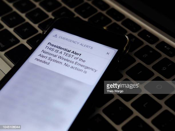 In this photo illustration a phone displays an emergency alert message that reads Presidential Alert THIS IS A TEST of the National Wireless...
