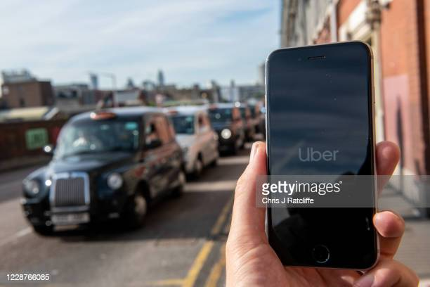 In this photo illustration a phone is held displaying the Uber logo in its app in front of a taxi stand at Waterloo station on September 28, 2020 in...