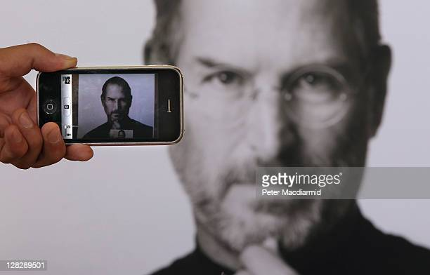 In this photo illustration a photographer takes a picture with his own iphone of a tribute to Apple Computer cofounder Steve Jobs placed outside The...