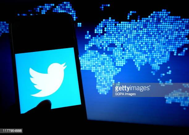 In this photo illustration a popular micro blogging and social networking service Twitter logo displayed on a smartphone