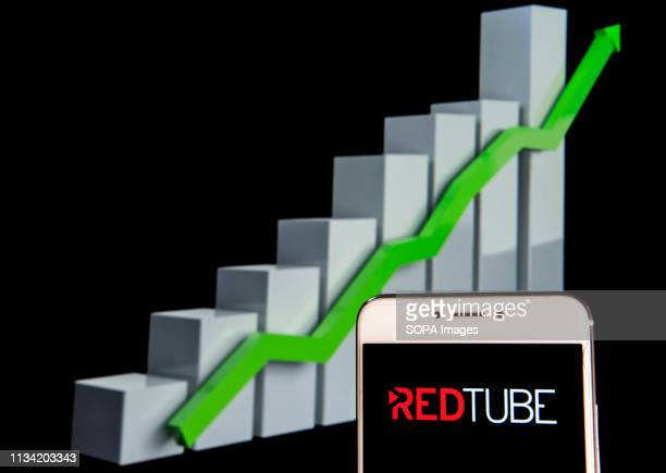 In this photo illustration a pornographic video sharing site Redtube logo is seen on an android mobile device with an ascent growth chart in the...