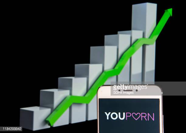 In this photo illustration a pornographic video sharing website YouPorn logo is seen on an android mobile device with an ascent growth chart in the...
