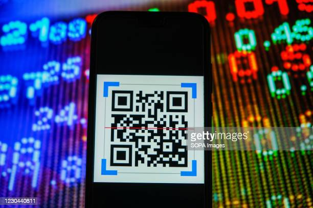In this photo illustration, a QR Code logo seen displayed on a smartphone with stock market prices in the background.