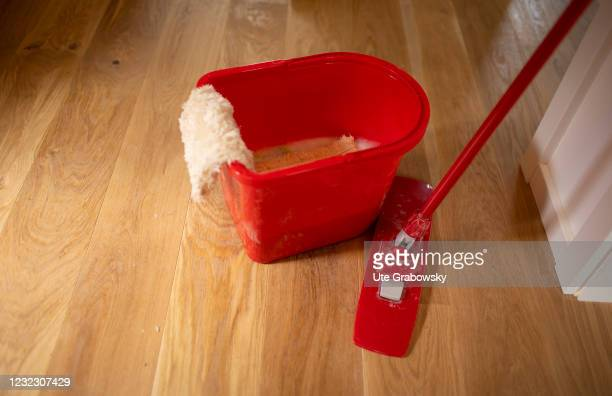 In this photo illustration a red cleaning bucket and mop on a parquet floor on April 13, 2021 in Bonn, Germany.