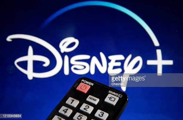 In this photo illustration, a remote control is seen in front of a television screen showing a Disney + logo on March 28, 2020 in Paris, France. At...