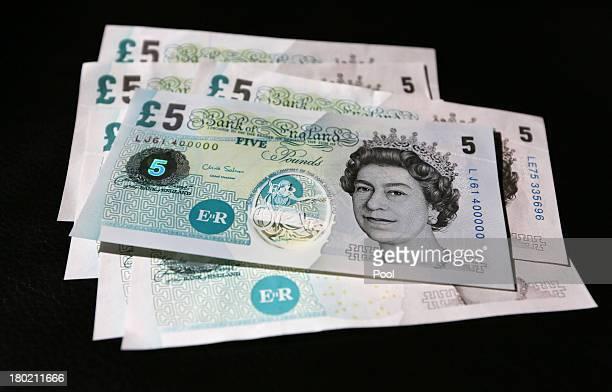 In this photo illustration a sample Polymer five pound British banknote sits on original five pound British paper banknotes during a news conference...