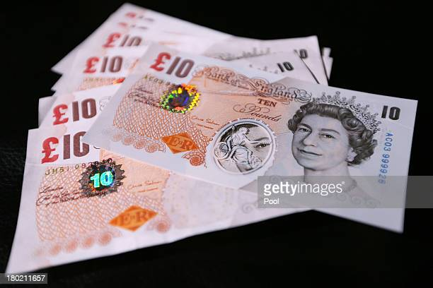 In this photo illustration a sample Polymer ten pound British banknote sits on original ten pound British paper banknotes during a news conference at...