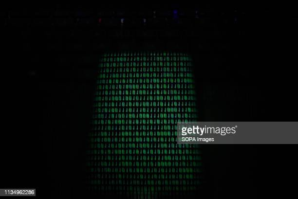 In this photo illustration a screen with binary code seen displayed on a smart phone
