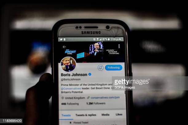 In this photo illustration a screenshot of the British Prime Minister Boris Johnson is seen on a mobile phone and a laptop