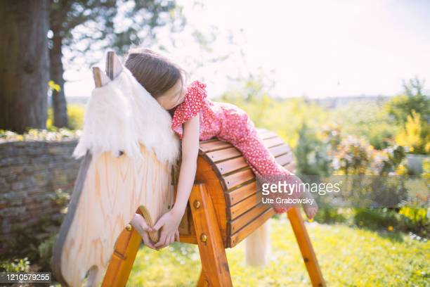 In this photo illustration a seven years old girl is riding a wooden horse on April 15, 2020 in Bonn, Germany.