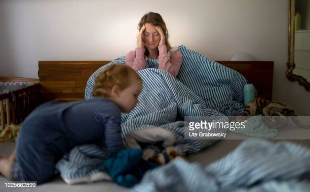 In this photo illustration a sick woman is sitting in her bed holding her head on July 08 2020 in Bonn Germany