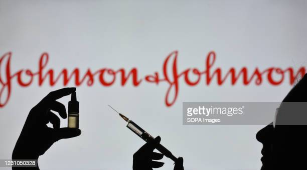 In this photo illustration a silhouette of a man holding a medical syringe and a vial seen displayed in front of the Johnson and Johnson logo on a...