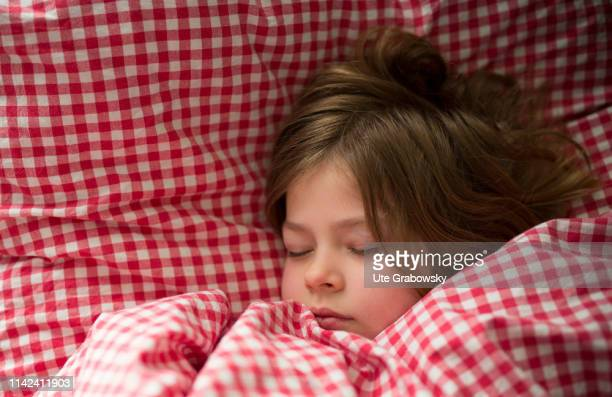 In this photo illustration a six years old girl is sleeping in checkered bed linen on April 07 2019 in Bonn Germany