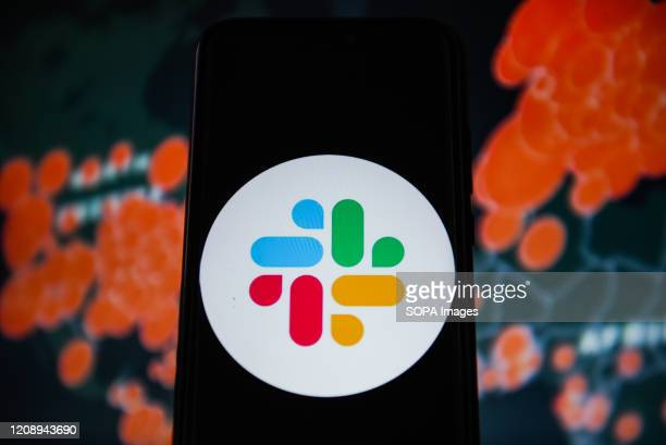 In this photo illustration a Slack logo is seen displayed on a smartphone with a World map of COVID 19 epidemic on the background.