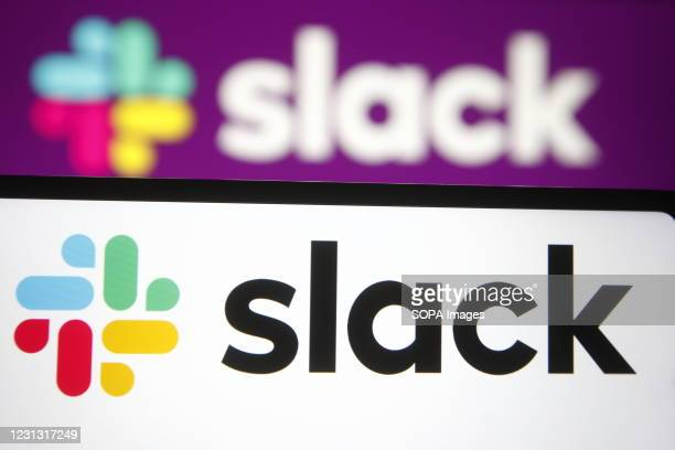 In this photo illustration a Slack logo of a business communication platform is seen on a smartphone and a pc screen.
