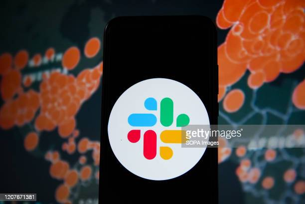 In this photo illustration a Slack logo seen displayed on a smartphone with a World map of COVID 19 epidemic on the background.
