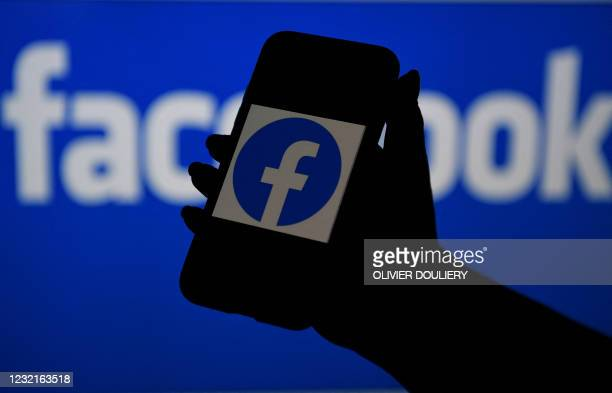 In this photo illustration, a smart phone screen displays the logo of Facebook on a Facebook website background, on April 7 in Arlington, Virginia -...