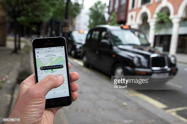 In this photo illustration a smartphone displays the 'Uber' mobile application which allows users to hail privatehire cars from any location on June...