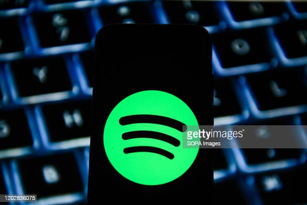 In this photo illustration a Spotify logo seen displayed on a smartphone.