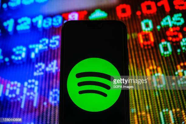 In this photo illustration, a Spotify logo seen displayed on a smartphone with stock market prices in the background.