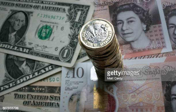 In this photo illustration, a stack of £1 coins is seen with the new £10 note alongside US dollar bills on October 13, 2017 in Bath, England....