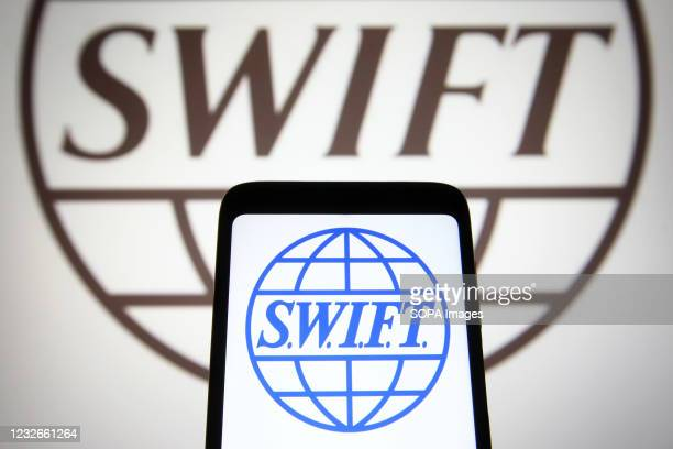 In this photo illustration a SWIFT logo is seen on a smartphone and a pc screen.