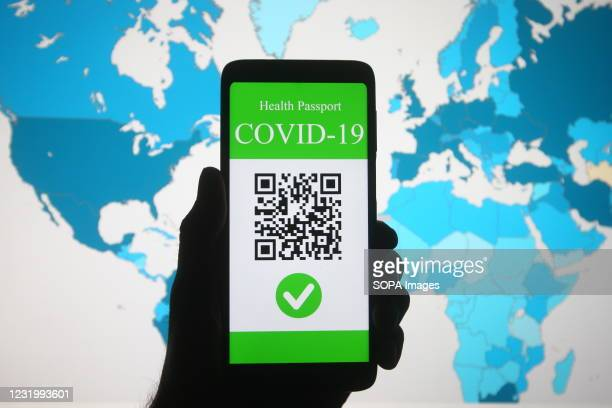 In this photo illustration, a symbolic COVID-19 health passport seen on a smartphone in front of the World Health Organization global map displaying...