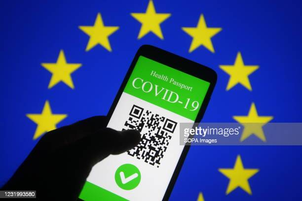 In this photo illustration, a symbolic COVID-19 health passport seen displayed on a smartphone screen in front of the EU flag. On March 17 the...
