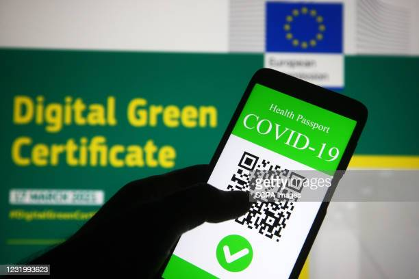 In this photo illustration, a symbolic COVID-19 health passport seen displayed on a smartphone screen in front of the European Commission information...