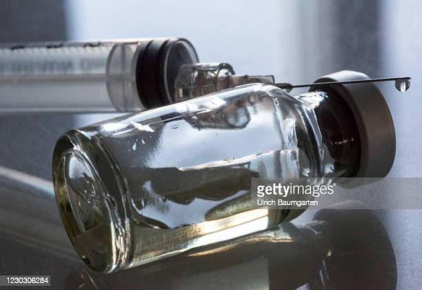 In this photo illustration, a syringe rests on a vial containing liquid on December 26, 2020 in Bonn, Germany. In Germany, vaccinations against the...