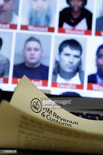 In this photo illustration a tax document is seen in front of a laptop screen showing the HMRC Flickr feed with the faces of their most wanted tax...
