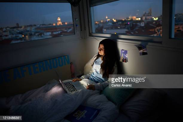 In this photo illustration, a teenage girl watches a series on the bed in her room on March 18, 2020 in Madrid, Spain. As part of the measures...