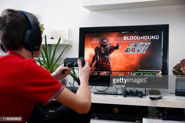 In this photo illustration a teenager plays the video game Apex Legends developed by Respawn Entertainment and published by Electronic Arts on a Sony...