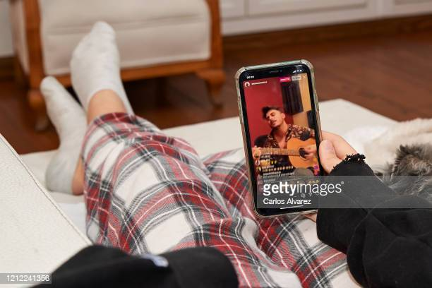 In this photo illustration A teenager watches Sienna's online concert at her home following the recommendation of staying at home to fight COVID19 on...
