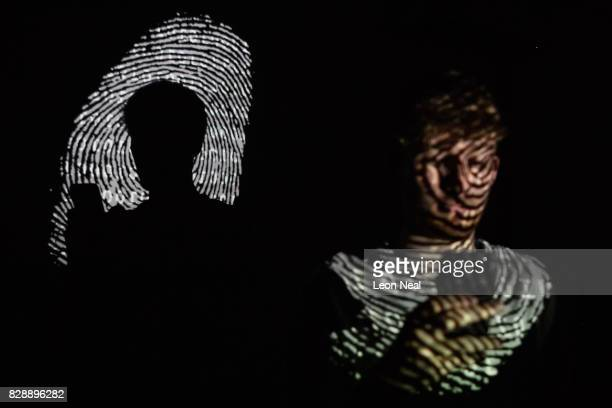 In this photo illustration, a thumbprint is projected onto a man as he holds a mobile phone on August 09, 2017 in London, England. With so many areas...