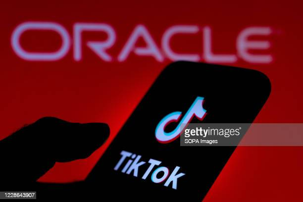 In this photo illustration a TikTok logo is seen displayed on a smartphone with an Oracle logo on the background.