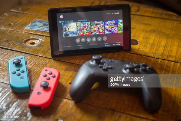 In this photo illustration a turned on Nintendo Switch with 2 JoyCon and a Pro Controller in front of it The Kyoto based video game company Nintendo...