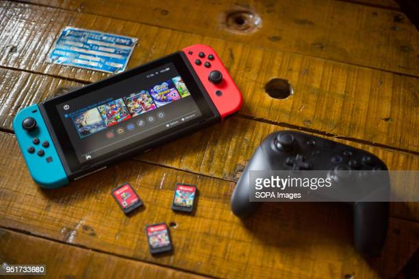 In this photo illustration, a turned on Nintendo Switch with 2 Joy-Con attached on it, a Pro Controller and 3 cartridge games. The Kyoto based video...