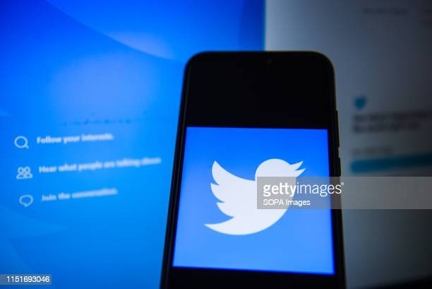 In this photo illustration a Twitter logo seen displayed on a smartphone