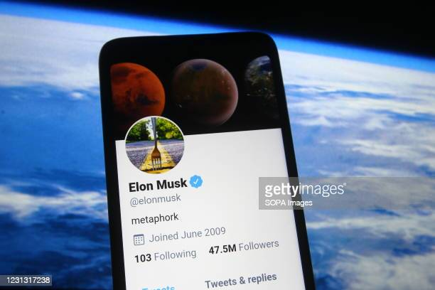 In this photo illustration a Twitter webpage of Elon Musk is seen on a smartphone screen in front of Spacex website.