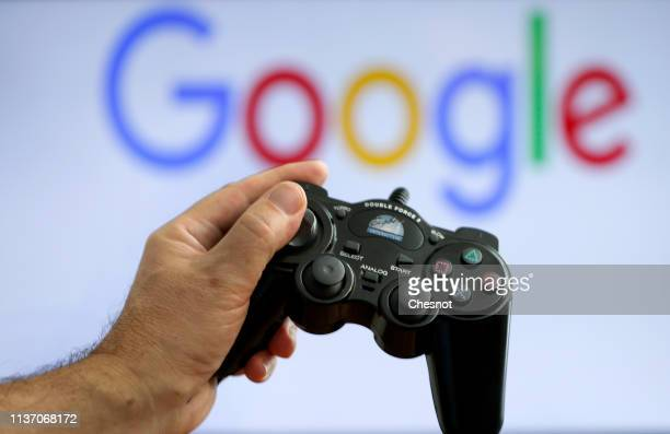 In this photo illustration a video game controller is displayed in front of a computer screen showing a Google logo on March 20 2019 in Paris France...