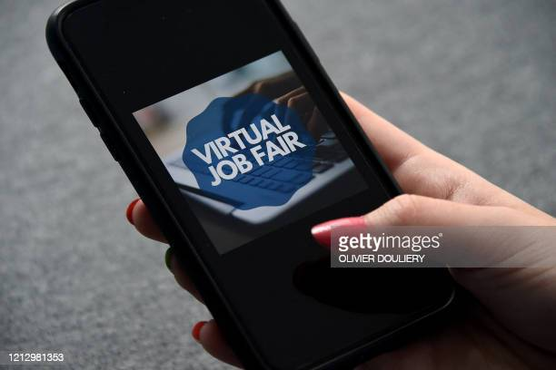TOPSHOT In this photo illustration a Virtual Job Fair app logo is displayed on a mobile phone screen on May 14 2020 in Arlington Virginia Another 3...