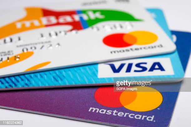 In this photo illustration a Visa credit card and Mastercard debit cards are seen displayed