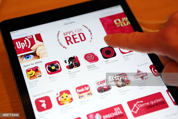 In this photo illustration a visitor tries out apps on an iPad at the Apple Store on December 1 2014 in Berlin Germany On World AIDS Day December 1...