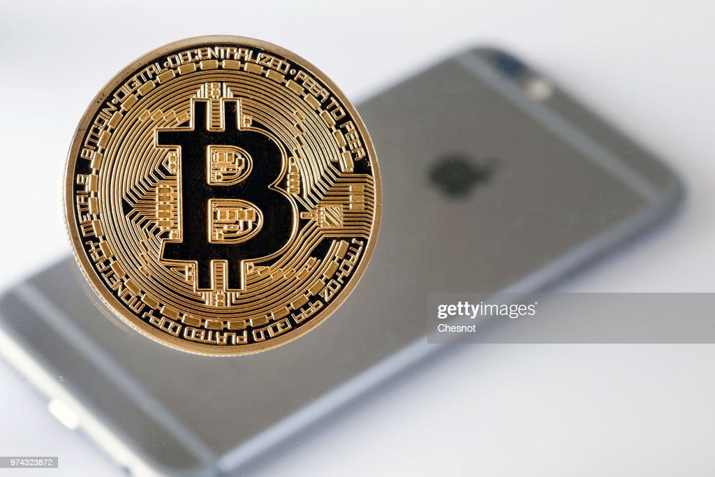 In this photo illustration, a visual representation of the Bitcoin Digital Cryptocurrency sits on display in front of an Apple iPhone 6 on June 14, 2018 in Paris, France. Apple will now ban from the mobile App Store any applications of its iPhones that mines cryptocurrencies. According to AppleInsider, the new guidelines of the App Store clearly prohibits the exploitation of an iOS device in order to mine cryptocurrencies.